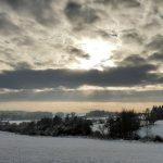 Zasněžená krajina s dramatickými oblaky.